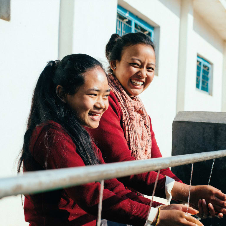 Bina (right) and a friend wash their hands at their school in Nepal. Photo: Tom Price/Tearfund