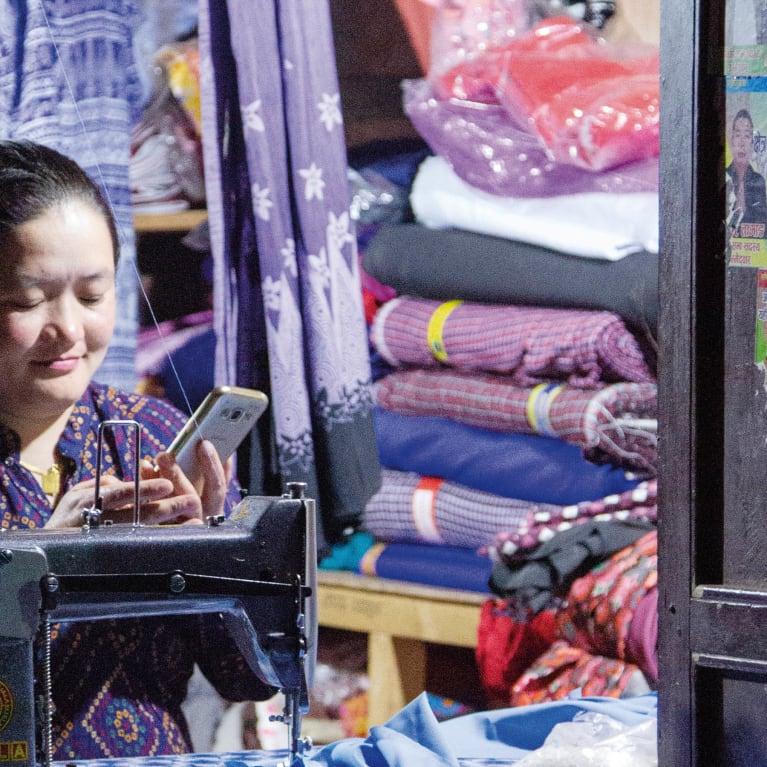 Shanti in Nepal checks her smart phone for news. Photo: Kit Powney/Tearfund