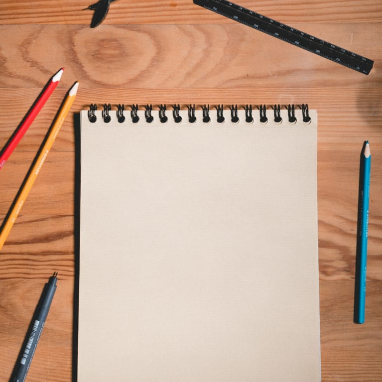 A blank sheet of paper on a desk with pens and pencils scattered around