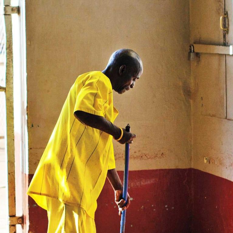 Um presidiário limpa o piso da entrada da prisão de Luzira, em Uganda. Foto: Andrew Philip