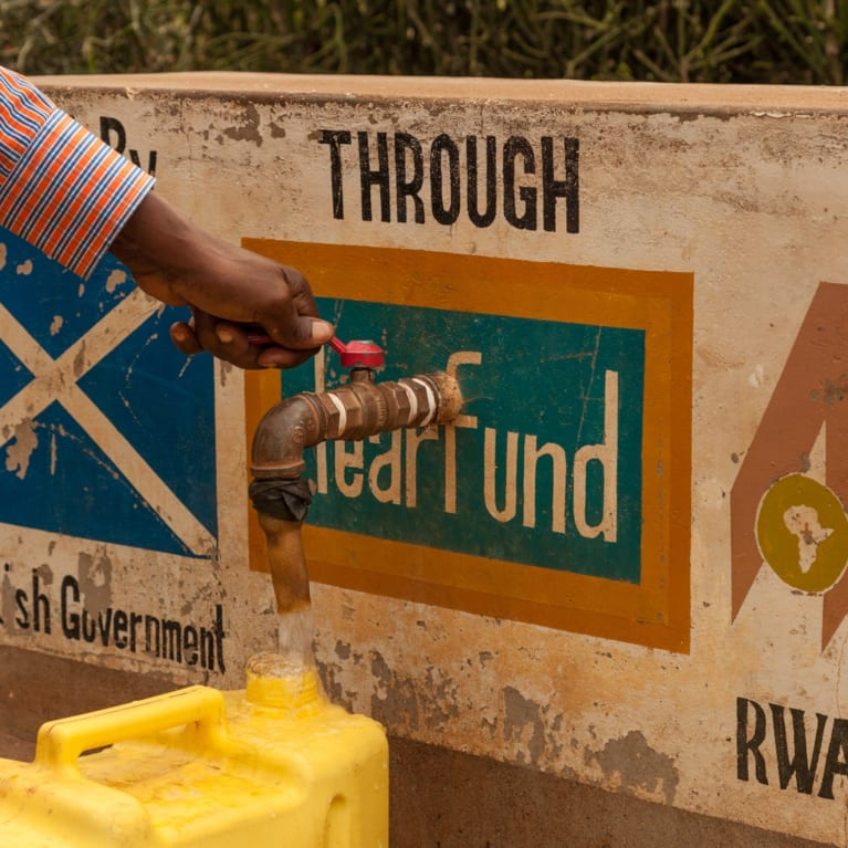 A member of the local community gathering water from a community water tap in the Gisagara district of Rwanda, where Tearfund are working with partner African Evangelistic Enterprise. Photo: Chris Hoskins/Tearfund