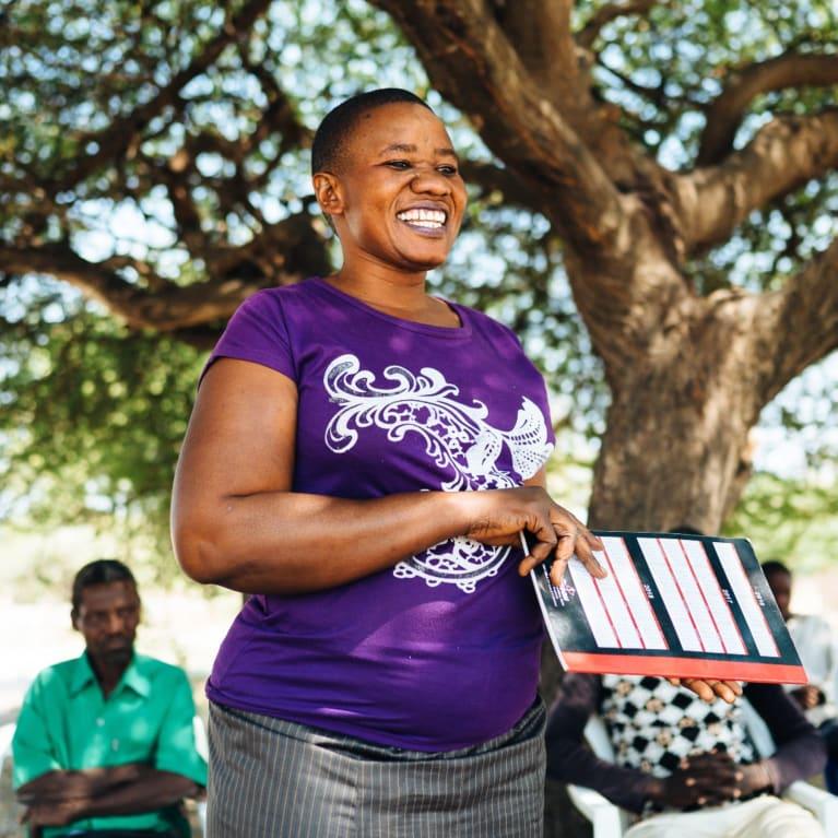 Christina Ndahani, responsible for the community's resources, speaks to members of the 'pamoja' self-help groups, gathered in Sasajila village.