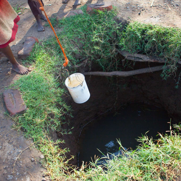 People collecting water from a dug well in rural Malawi. Photo: Clive Mear/Tearfund