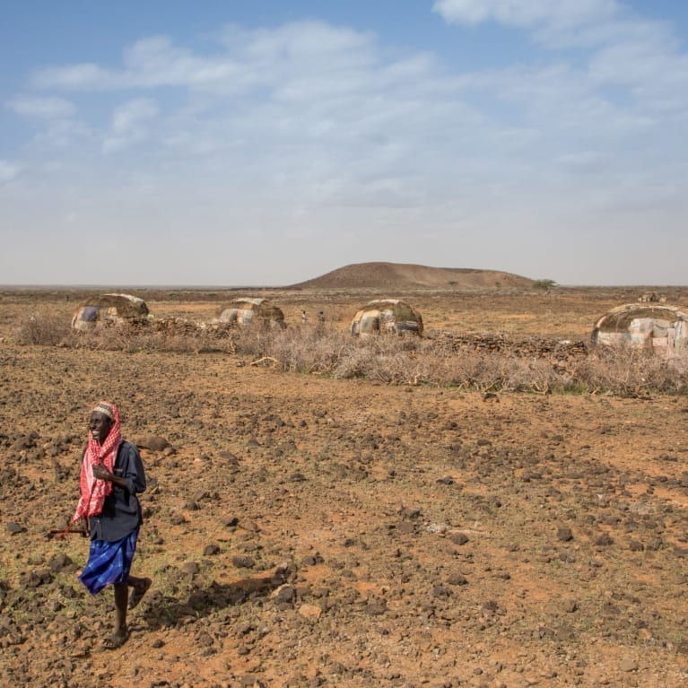 A man outside his family home in the village of Wara, in northern Kenya. Already an arid landscape, the communities here must move from place to place with their goats to make a living.