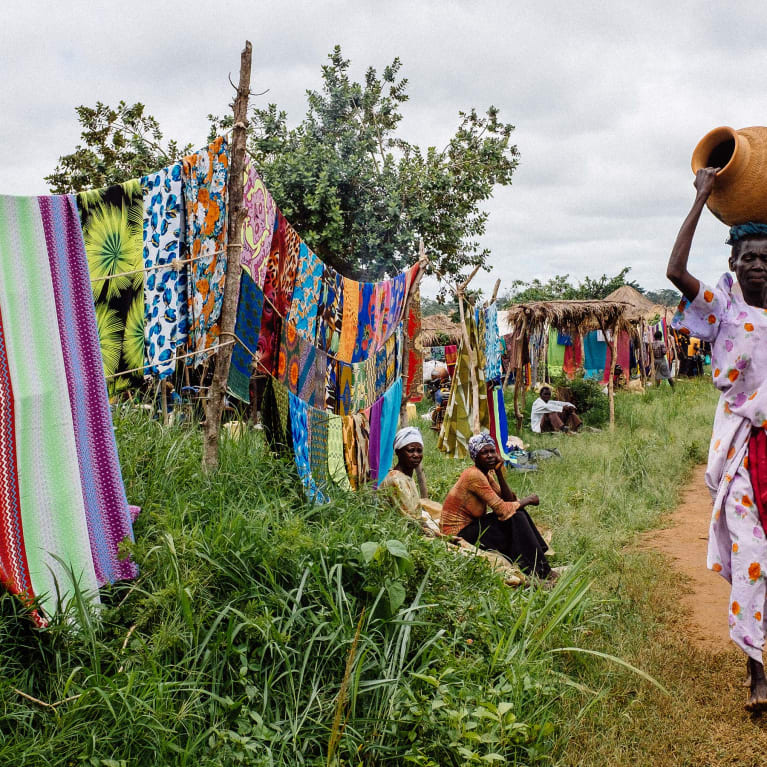 A community in Uganda where brightly coloured fabric is sold at the side of the road and a woman walks past carrying an earthenware pot.