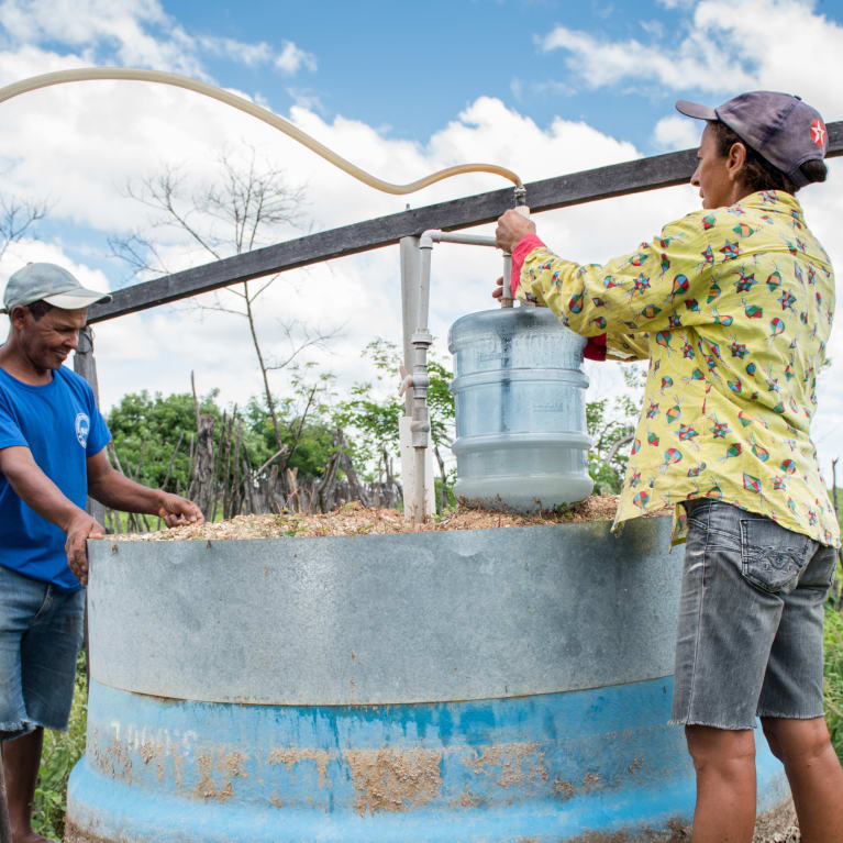 Two people use a biodigester to get fuel.