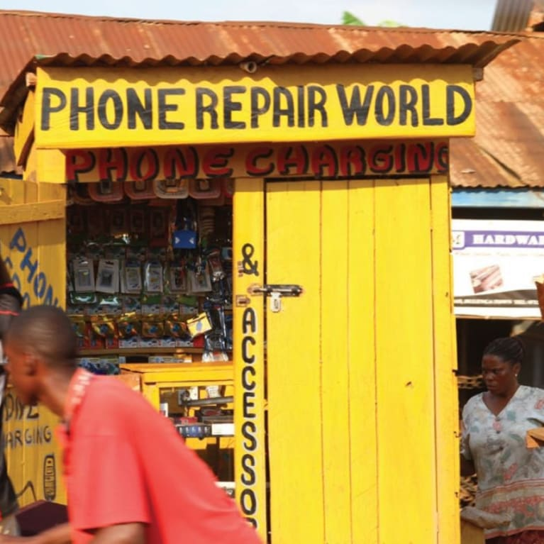 A roadside phone repair shack displays recycled phones in an African marketplace