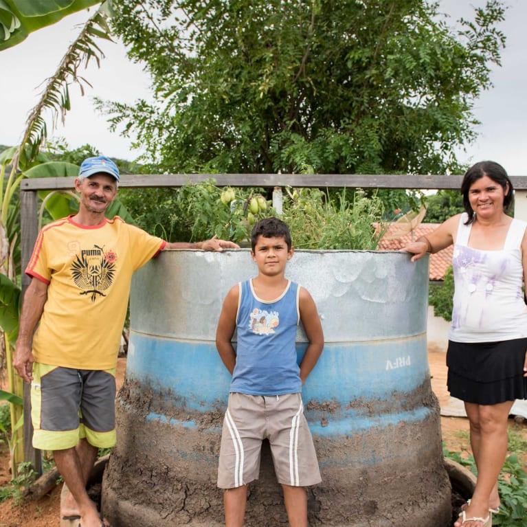 Uma família de agricultores com seu biodigestor, o qual transforma resíduos em gás de cozinha. Foto: Eleanor Bentall/Tearfund