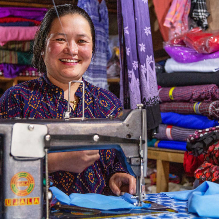 Off-grid renewable electricity enables a woman in Nepal to continue working in her tailoring business after dark.