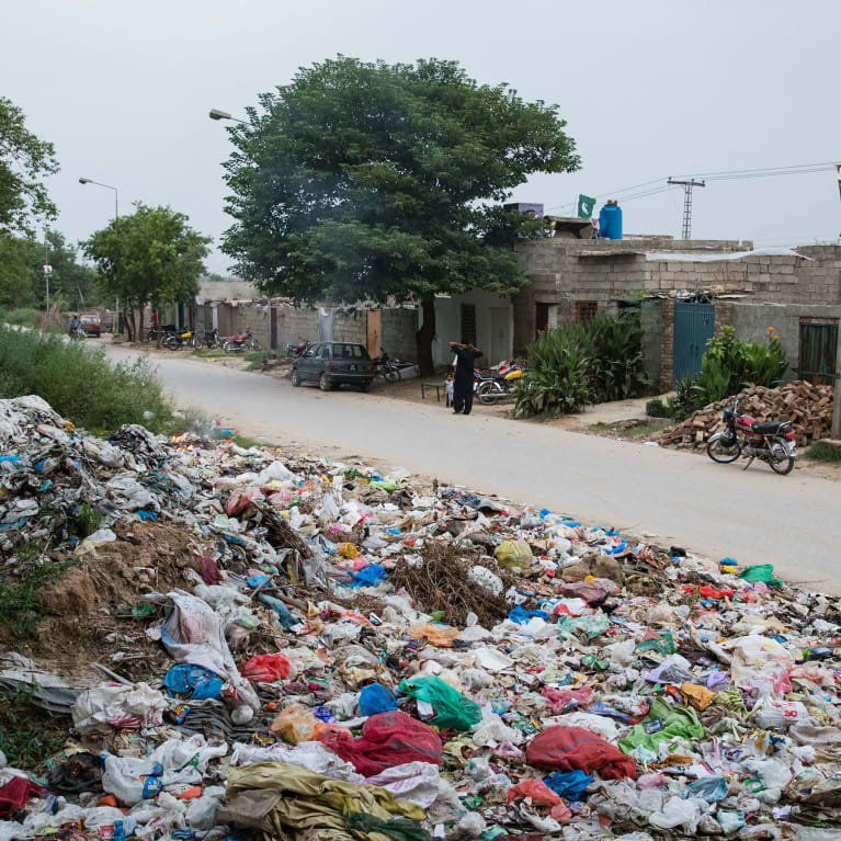 Waste is discarded at the edges of an informal settlement in Islamabad, Pakistan.