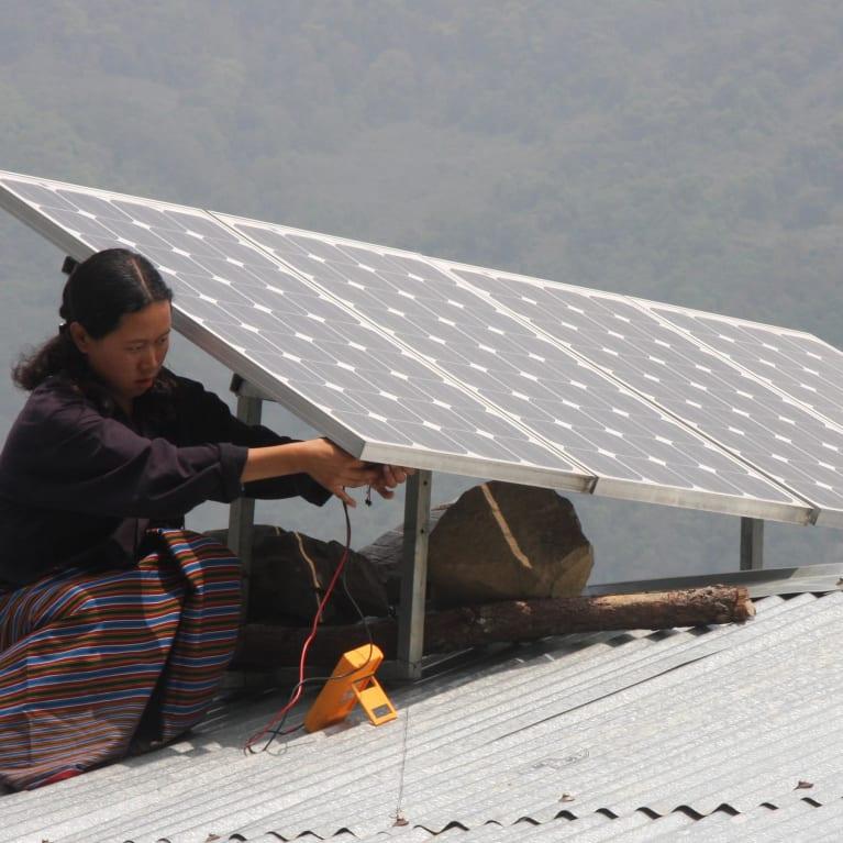 Woman installing solar panels on a roof in Bhutan.