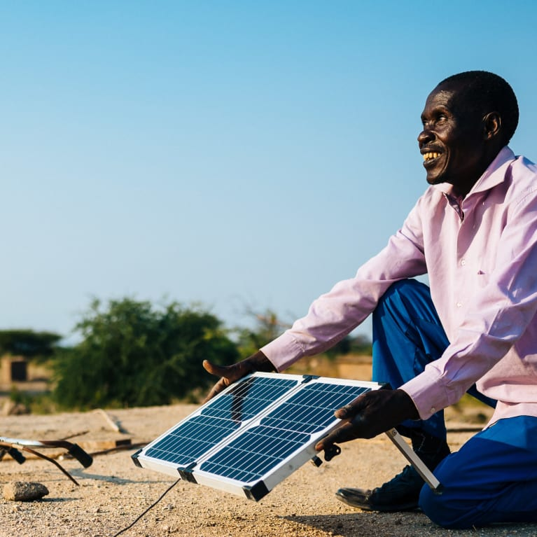 Man positions a solar panel on the roof of his house in Tanzania.