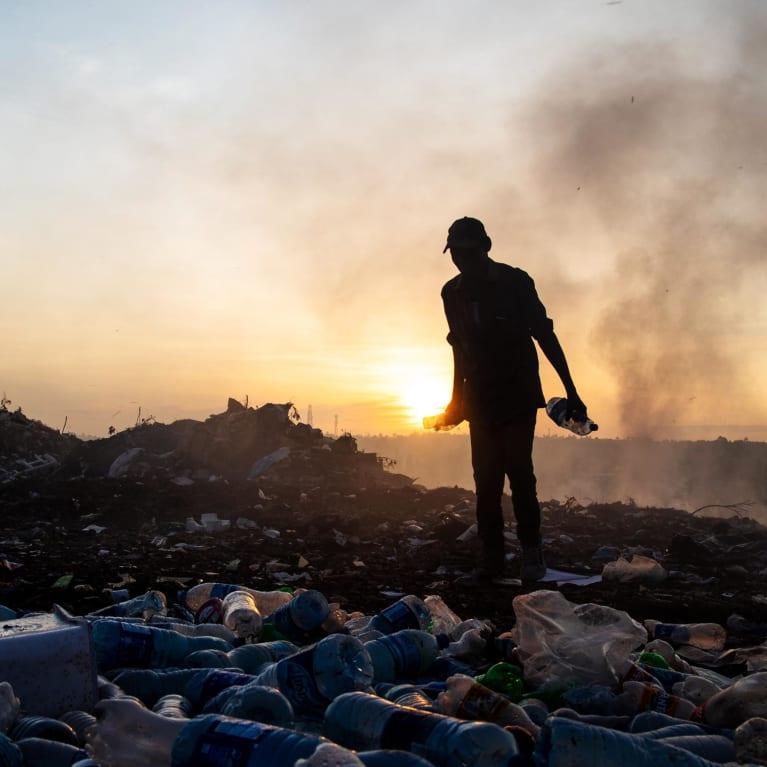 Um catador de lixo juntando garrafas plásticas em um lixão na Tanzânia. Foto: Daniel Msirikale/Tearfund