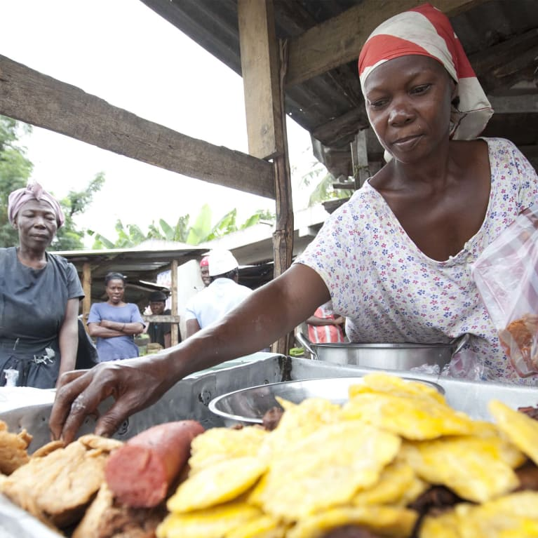 Una mujer empresaria vende comidas calientes en su puesto de un mercado en Haití. Foto: Warren Allott/Tearfund