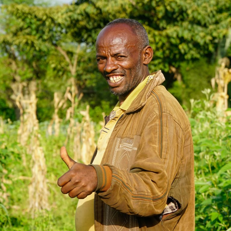 A farmer called Emiyas from Ethiopia smiling in a field surrounded by trees