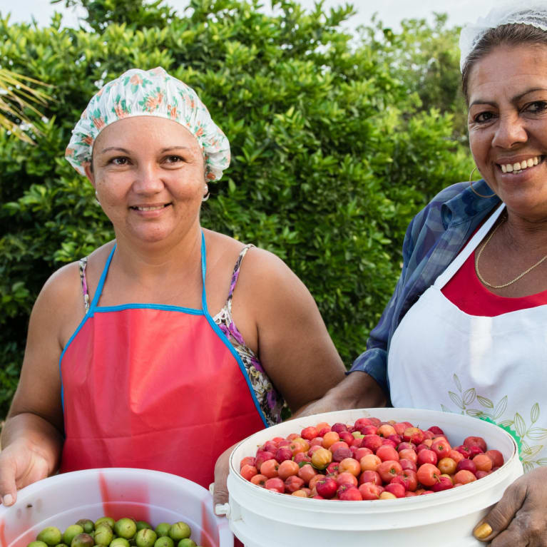 Two women in northeast Brazil hold up buckets of fresh fruit