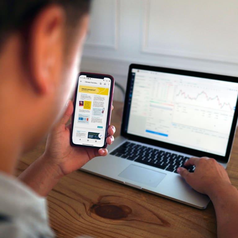 Un homme travaille sur son ordinateur portable et son téléphone portable