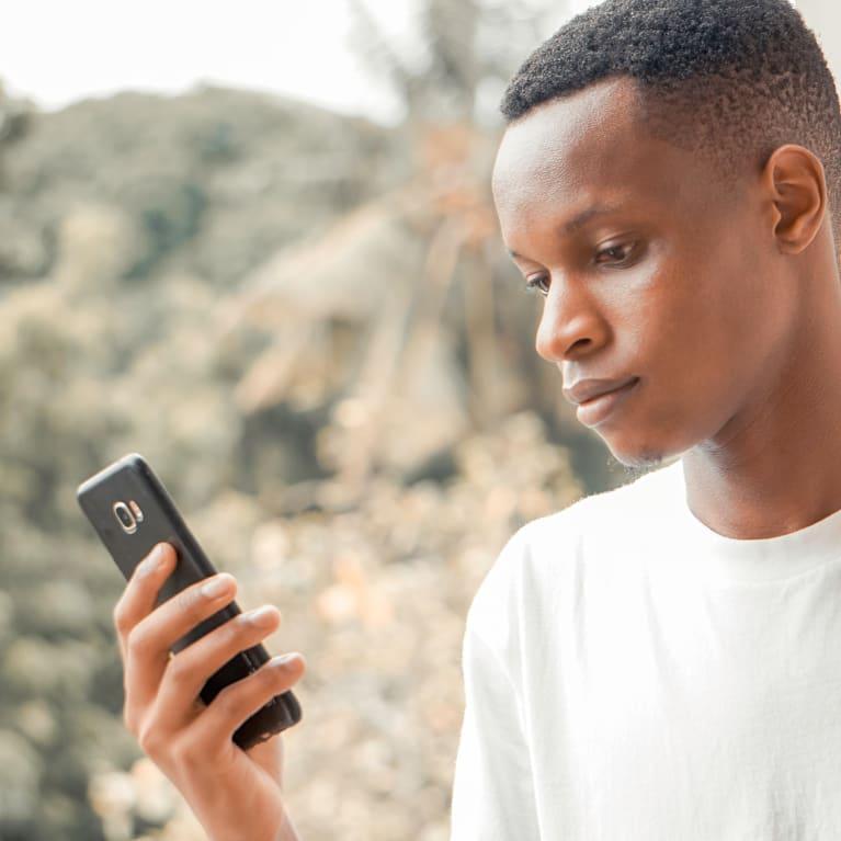 Um homem olha para o seu telefone celular