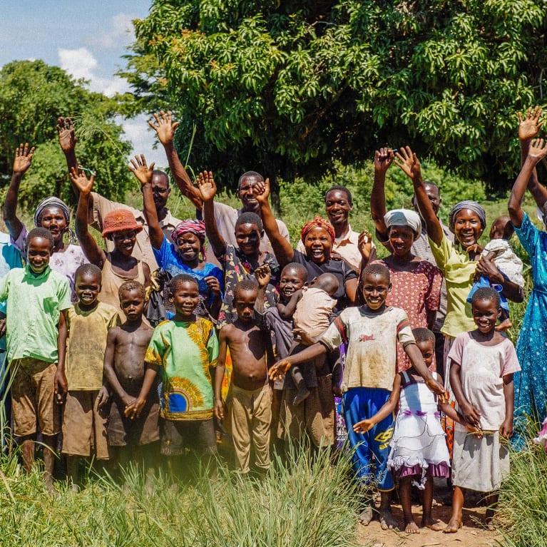 Membros de uma comunidade sorrindo e acenando para a câmera em Uganda, na África. Foto: Andrew Philip/Tearfund