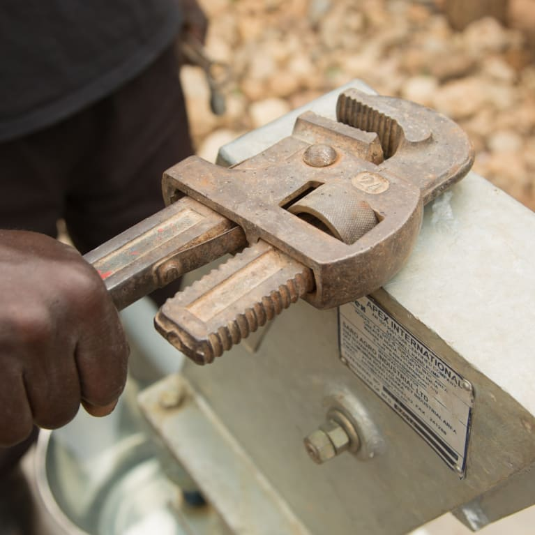 A villager maintains and repairs their water pump