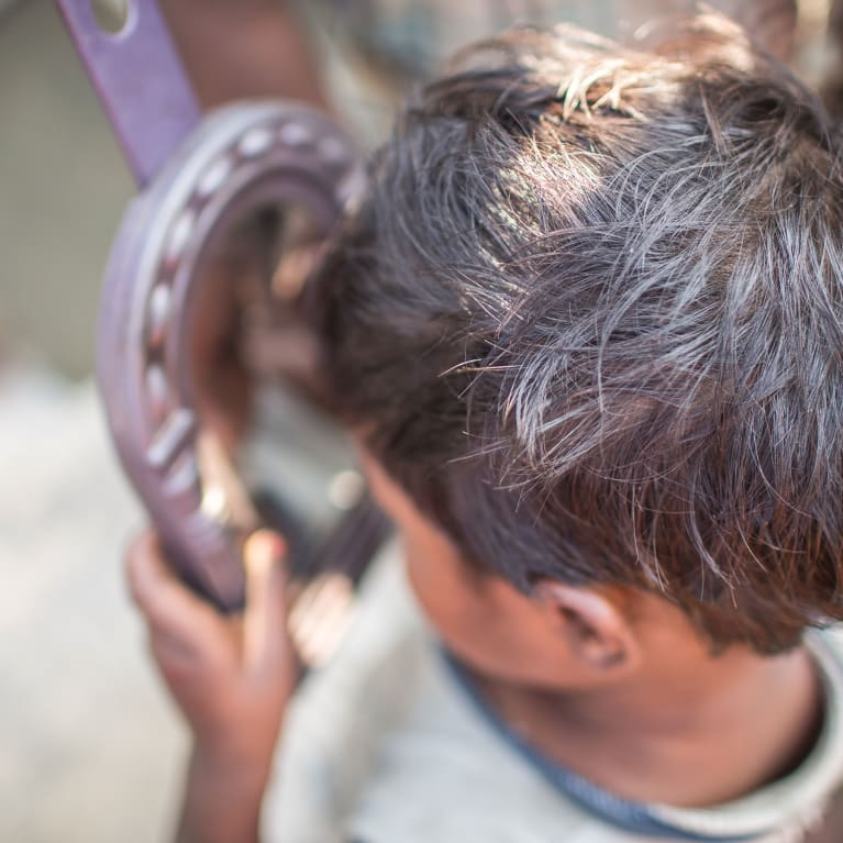 A young boy in Bihar, India, looks at his reflection in a mirror