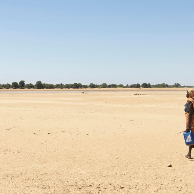 Femme traversant le lit asséché d'une rivière, au Tchad, pour trouver de l'eau. Photo : Peter Caton/Tearfund