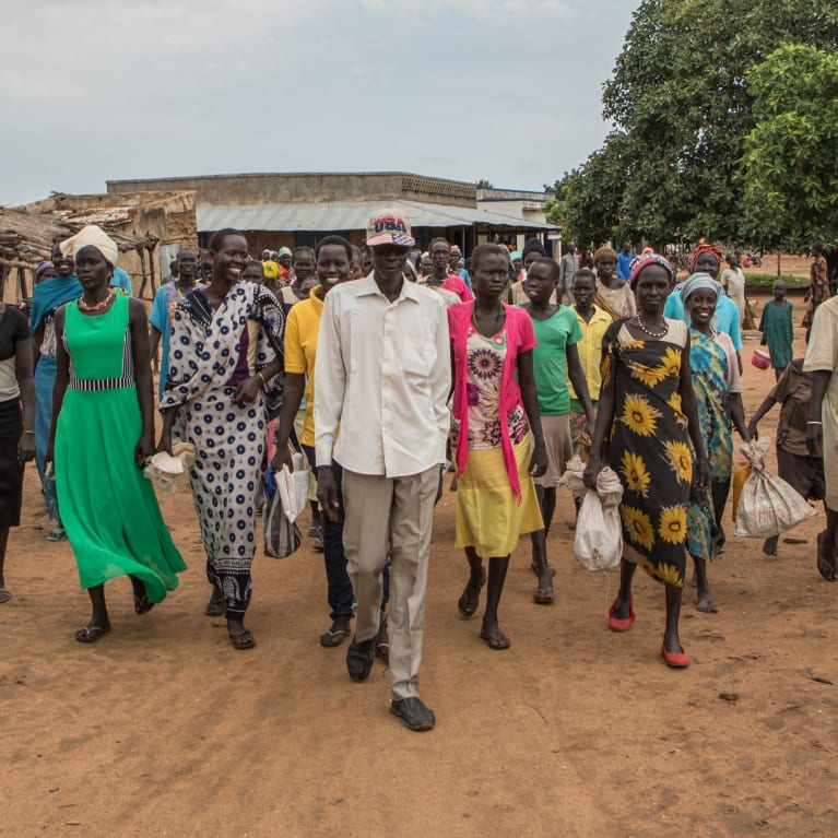 Women with food vouchers walk to the market to receive their food items from local vendors in South Sudan