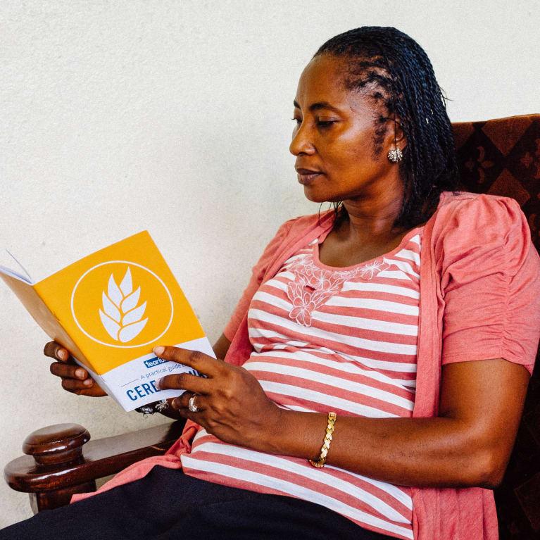 Une femme lit la brochure de Tearfund « Guide pratique des banques de céréales ». Photo : Andrew Philip/Tearfund