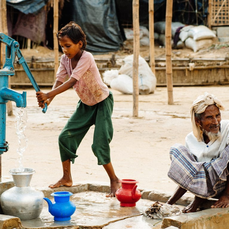 A child collects water at Cox's Bazar refugee camp | Credit:Andrew Philip/Tearfund