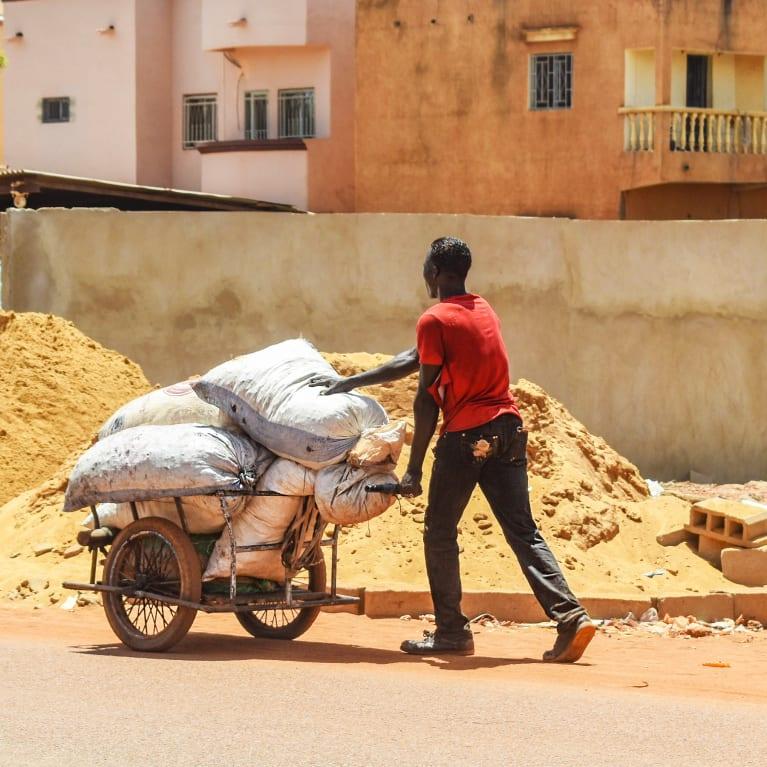 A man pushes a wheelbarrow of sacks through a construction site | Credit: Steve Goddard/Tearfund