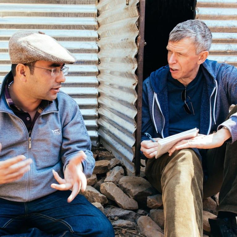 Tearfund's Nepal Response Manager, Rajan Ghimire, translates for Nigel Harris, Tearfund CEO, in Basanta village in Nepal. Photo credit: Tom Price/Tearfund