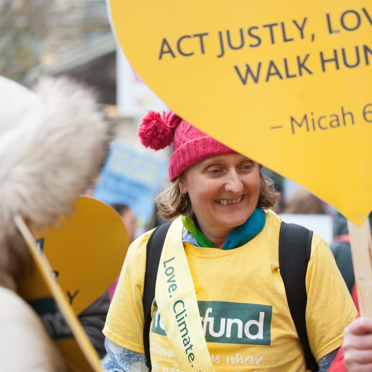 A climate march with placards showing Micah 6:8 (Clive Mear/Tearfund)