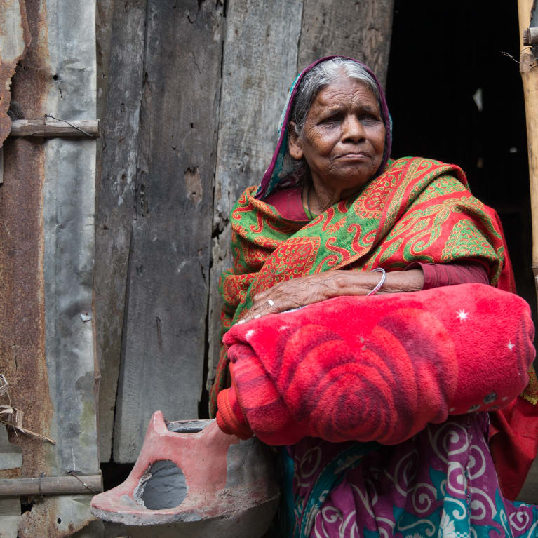 Mabia clutches a stove and blanket given to her after she lost everything in the 2017 floods. But what if Mabia could be protected from the effect of future flooding and disaster? Photo: Ralph Hodgson/Tearfund