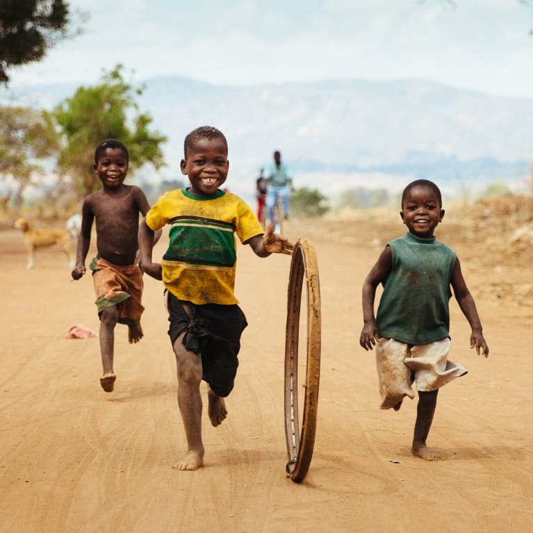 Group of children running happily down the road together