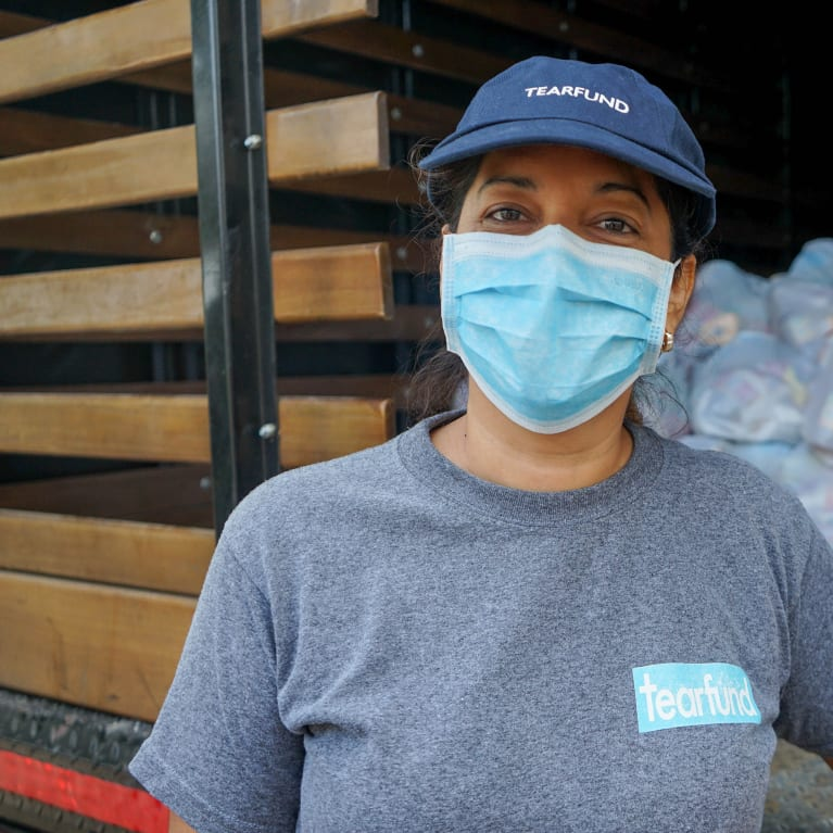 A woman in Tearfund clothes working while wearing a face mask