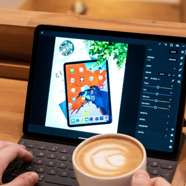 A person editing an image on their tablet, along with a cup of coffee