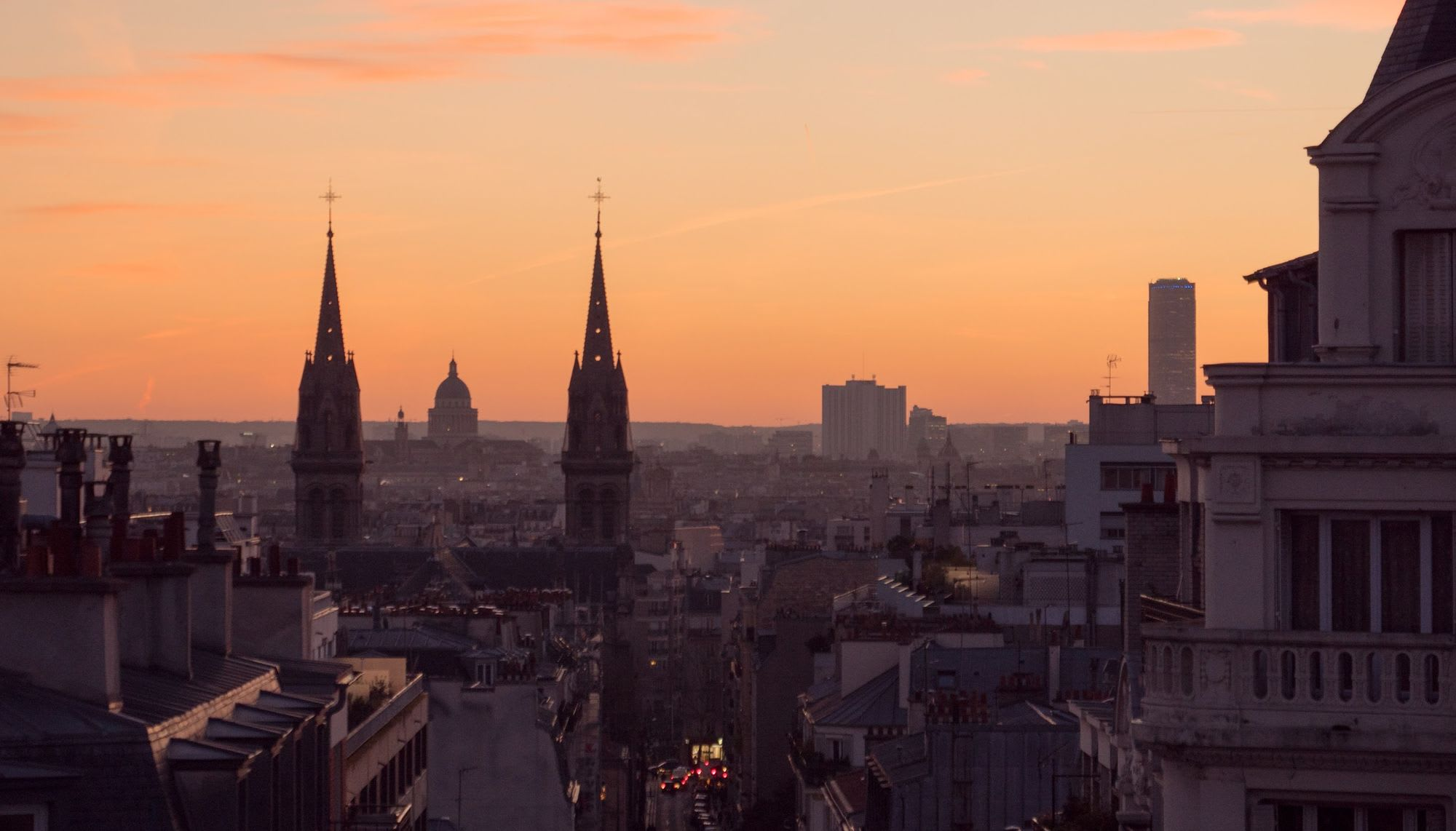 Photo of a church, the Pantheon et Montparnasse shot over the roofs of Paris at Sunset