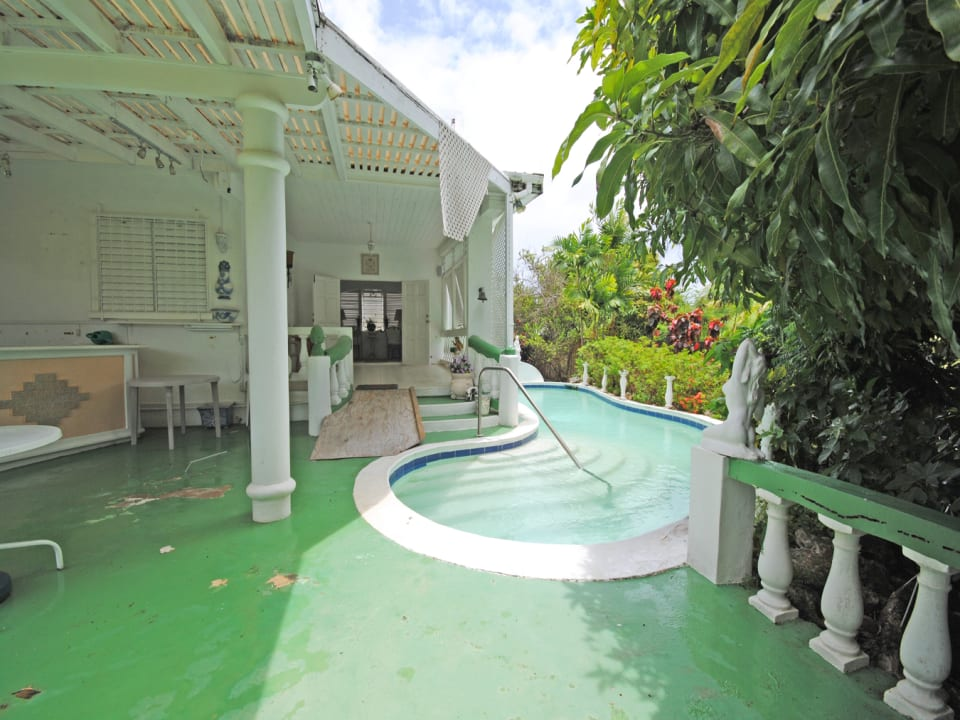 Spacious paved terrace connects bar veranda and pool