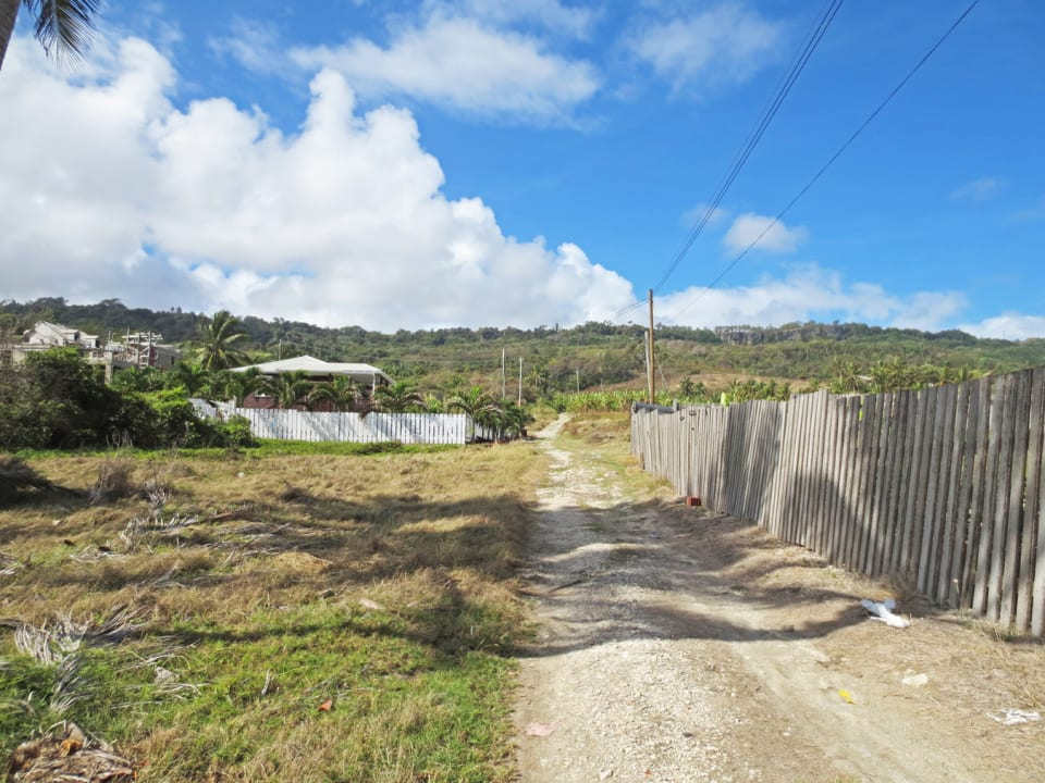 Unpaved road leading to the lot