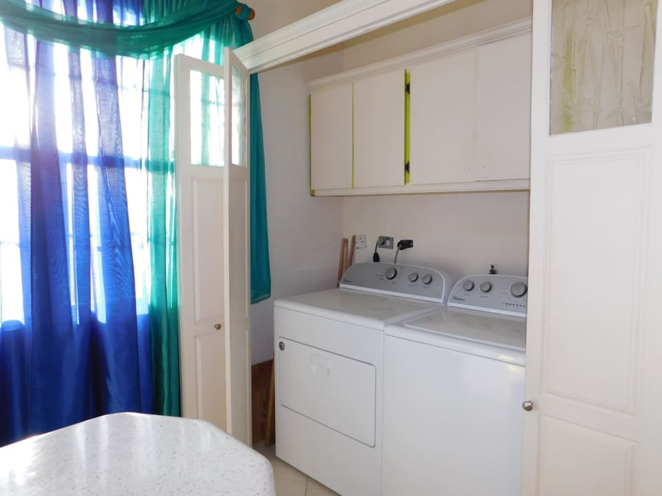 Washer and Dryer stored in a large cupboard adjacent from the spacious kitchen