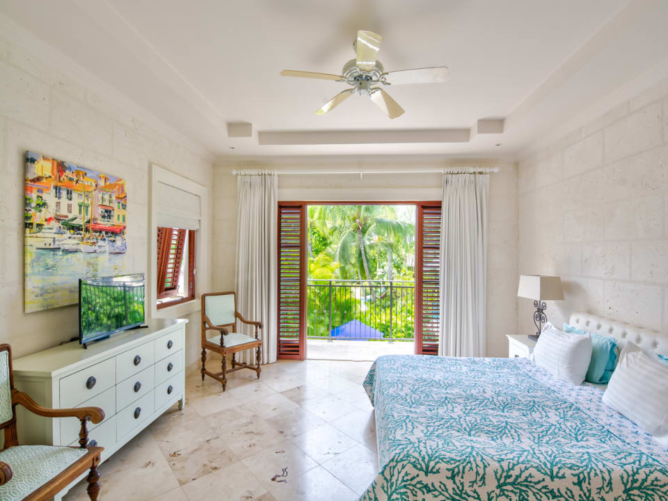 Primary bedroom with private terrace overlooking the gardens and pool