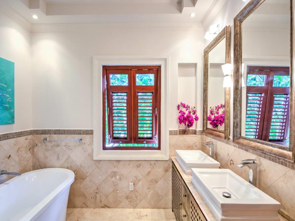 En suite with bathtub, walk in shower and double vanity in primary bedroom
