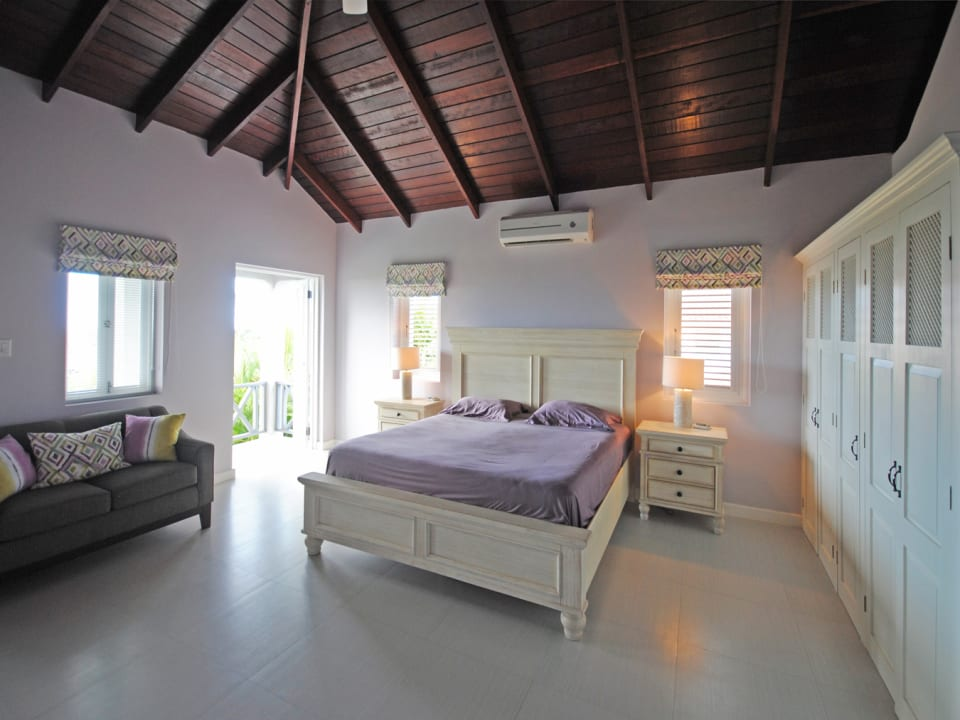 Second master bedroom on first floor opens to balcony with sea views
