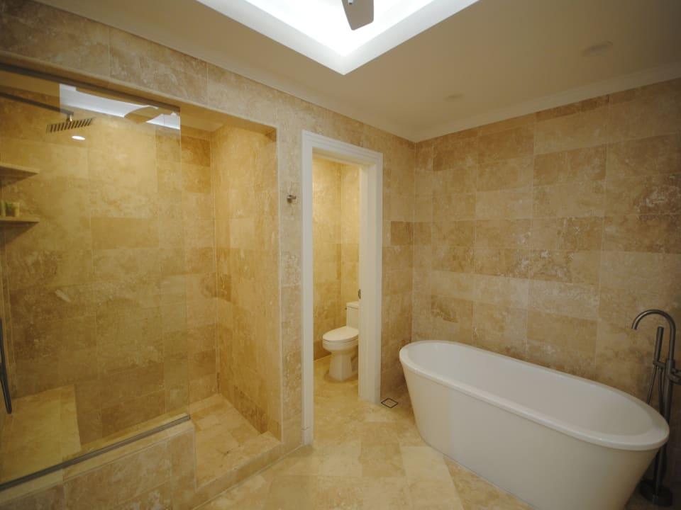 Main bathroom has a deep tub and shower
