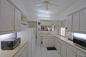 Fitted kitchen and laundry room beyond