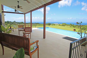Partially covered pool deck with sea views