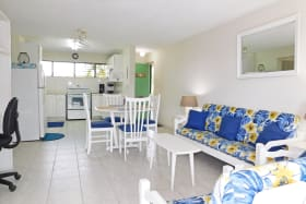 Open plan living and dining area with a desk and small bar area opposite