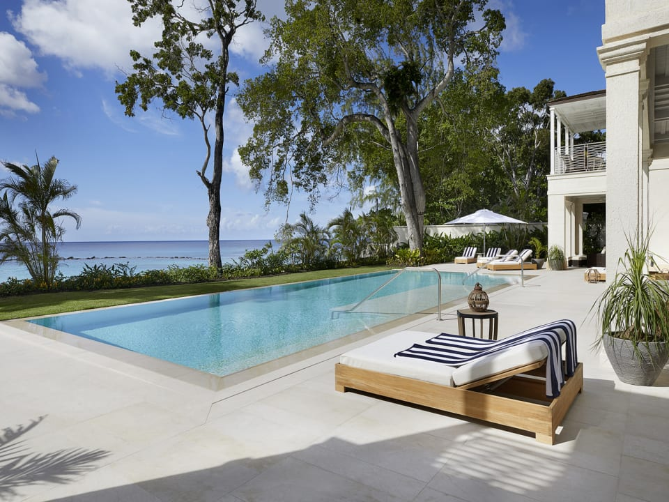 Expansive pool deck with mature mahogany trees framing the view