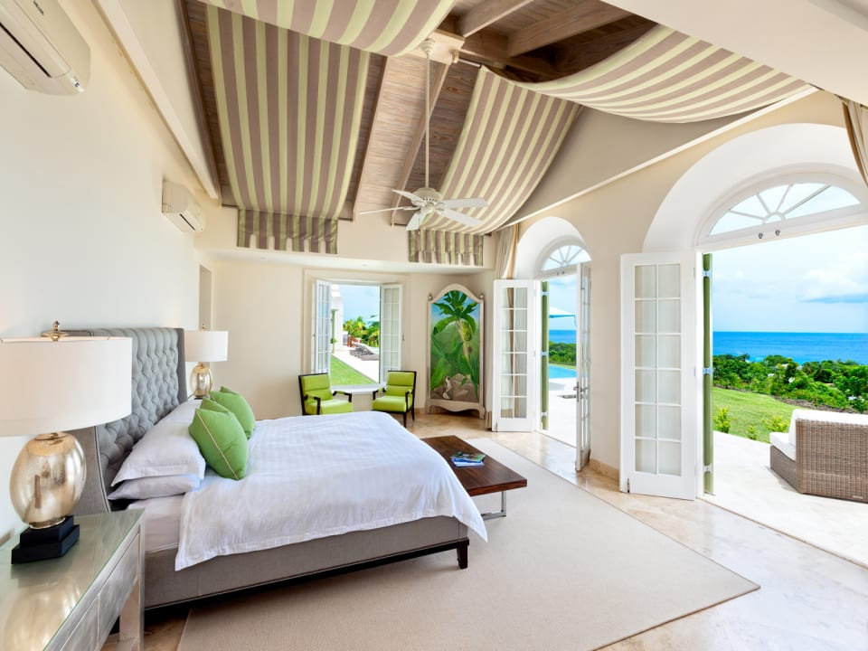 Spacious master bedroom opens to balcony with sea and pool views