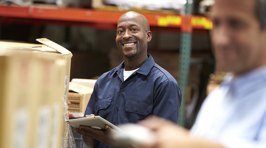 Male warehouse worker smiles after being praised by his team leader